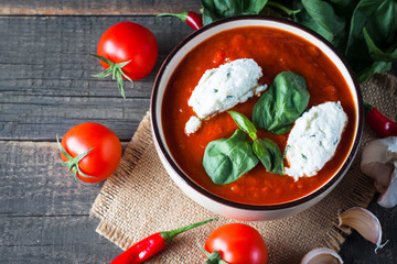 Chili tomato soup with sour cream sauce, cottage cheese, basil and red hot peppers on wooden background. Healthy, vegan and dieting lunch and dinner concept.