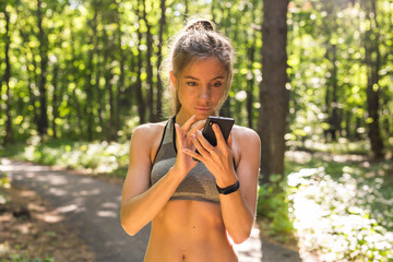 Active girl using fitness tracker smart watch jogging on summer nature outdoors looking at health data during sports activity