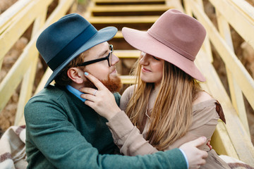 Stylish lovers in the hats look at each other with tenderness and love. Close-up portrait