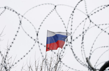 The Russian flag is seen through barbed wire as it flies on the roof of the Russian embassy in Kiev