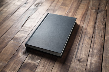 Blank black hardcover book on vintage wood table background.
