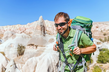Hiker with backpack travelling among Cappadocia fairy chimneys at summer, concept of tourism in middle east