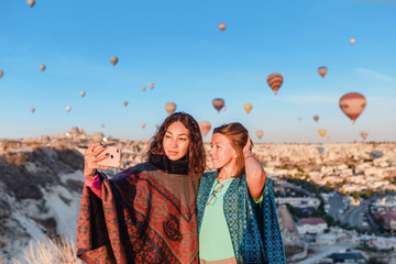 traveler enjoying valley view and making selfie on a phone with wonderful balloons flight over Cappadocia valley in Turkey