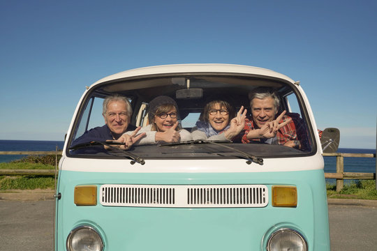 Portrait of senior people through vintage camper van windshield