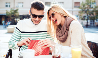 Shopping time. Young couple enjoying in a coffee after shopping. Consumerism, lifestyle concept