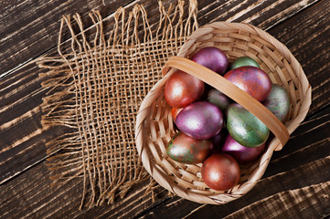 Easter eggs in a basket on an old wooden background.