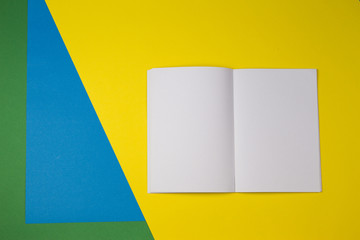 Open blank paper notebook with yellow, blue and green color background.