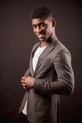 side view photography of smiling African man trying on coat isolated on the black background