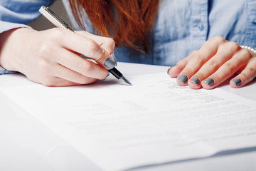 Beautiful business woman signing contract.