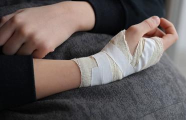 Child hand with gauze bandage on it.