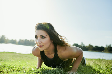 Determined young woman doing pushups on grass by lake