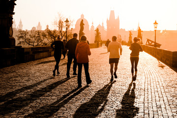 Runner athletes have morning jogging workout on Charles Bridge in Prague, Czech Republic. Healthy lifestyle and active start of a day.