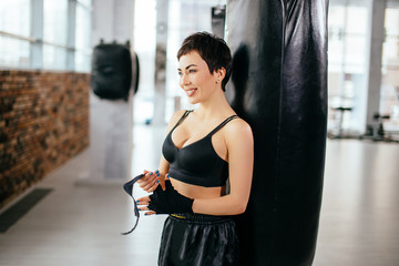 side view shot of smiling athlete wrapping black bandage on hands in front of punching bag at fitness class. preparation for boxing practise