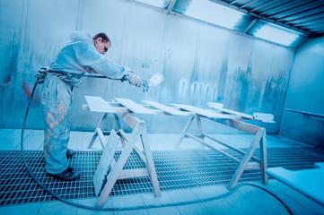 Man painting furniture details. Worker using spray gun. Toned image.