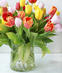 A bunch of fresh multicolored flowers in a transparent glass vase. Rustic style, selective focus