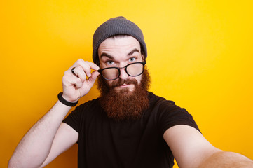 Bearded man with eyeglasses taking selfie