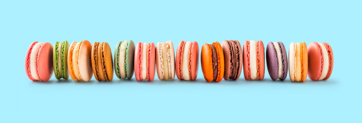 French macarons large group lined up on light blue background in studio