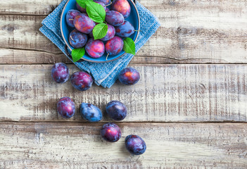 Plums fresh overhead colorful arrangement with green leaves on blue plate and cloth on white rustic wooden table in studio