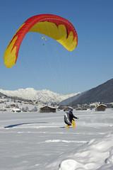 gleitschirmfliegerlandung im winter im stubaital