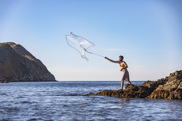 Man throwing fishing net in ocean while standing on a rock