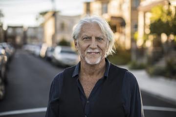 Portrait of smiling senior man standing on street in city