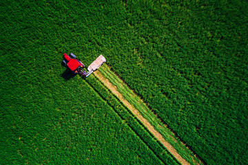 Tractor mowing green field, aerial view