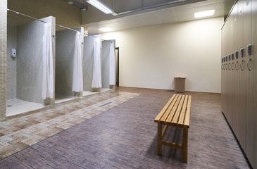 Public shower interior with everal showers and lockers in locker room in luxury fitness spa centre