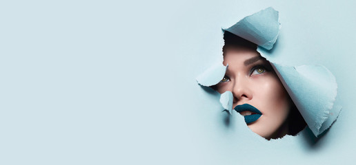 the face of a young beautiful girl with a bright make-up and puffy blue lips peers into a hole in...