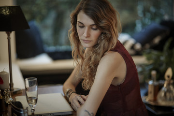 Serious young woman sitting at table