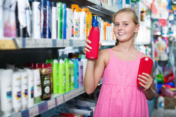 Smiling girl holding shampoo and conditioner in the hand
