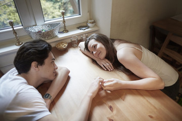 Young couple in love sitting on table at home looking at each other