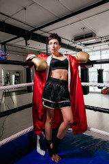 full length photo of young pleasant boxer woman in boxing equipment standing on ring.challenge to fight