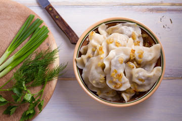 Plate of pierogi or varenyky, vareniki, Dumplings, filled with beef meat and served with fried onion. Pyrohy - dumplings with filling. View from above, top, overhead