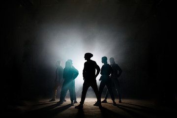silhouette of group breakers dancing headed by leader on stage
