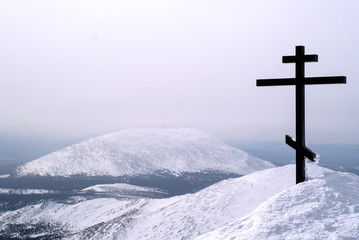 orthodox cross on top of the mount Konzhakovskiy Kamen against the background of the surrounding winter mountains