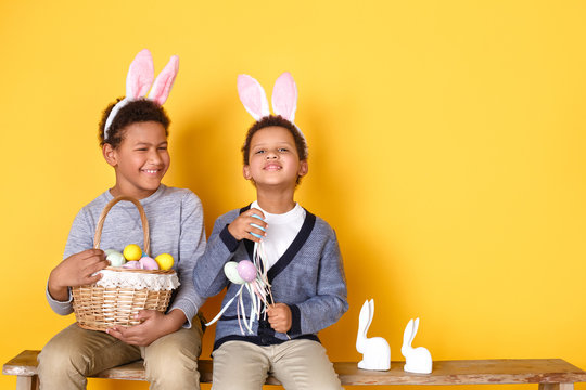 Two boys in bunny ears studio isolated on yellow wall easter celebration concept sitting holding basket with eggs talking