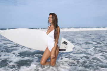 Surfer girl in a white swimsuit goes to the blue ocean, with a white surfboard