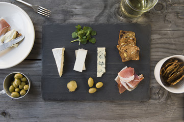 Overhead view of charcuterie and cheese on slate background