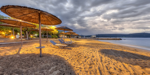 Wall Mural - Reed parasols on empty beach in twilight