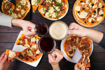 Friends eating pizza. Top view on male hands clinking mugs with beer over table with many pizzas. Party, friendship, pub, restaurant concept
