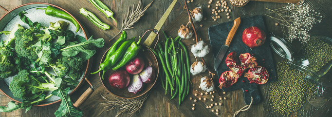 Winter vegetarian, vegan food cooking ingredients. Flat-lay of seasonal vegetables, fruit, beans, cereals, kitchen utencils, dried flowers, olive oil over wooden background, top view, wide composition