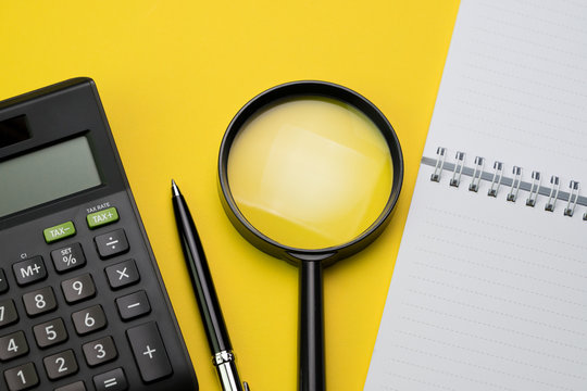 Flat lay or top view of black pen, calculator, magnifying glass and white notepad on vivid yellow background table with blank copy space, math, cost, tax or investment calculation