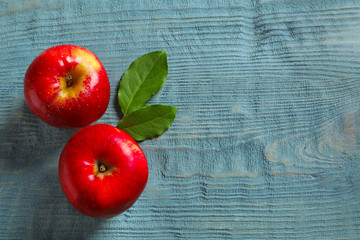 Ripe red apples on wooden background, flat lay