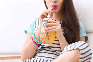 Young woman with tasty refreshing lemonade indoors