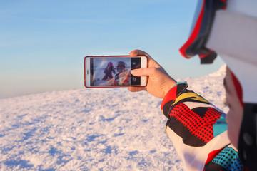 Woman taking selfie on top of snowy hill at ski resort. Winter vacation