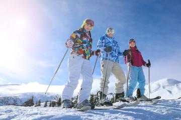 Friends on ski piste at snowy resort. Winter vacation