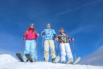 Friends on ski piste at snowy resort. Winter vacation