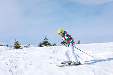 Woman skiing on piste at snowy resort. Winter vacation