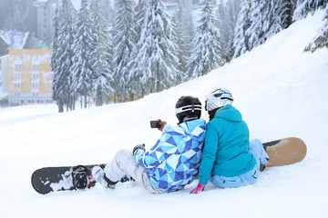 Snowboarders taking photo on ski piste at snowy resort. Winter vacation
