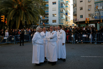 """Penitents look on before taking part in the procession of """"El Cautivo"""" brotherhood during Holy Week in Malaga, southern Spain"""